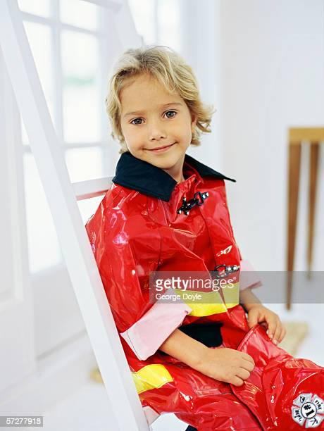 Side profile of a boy sitting on a step ladder, pretending to be a fireman
