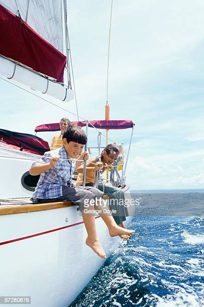 Side profile of a boy with a girl sitting on a sailboat and smiling