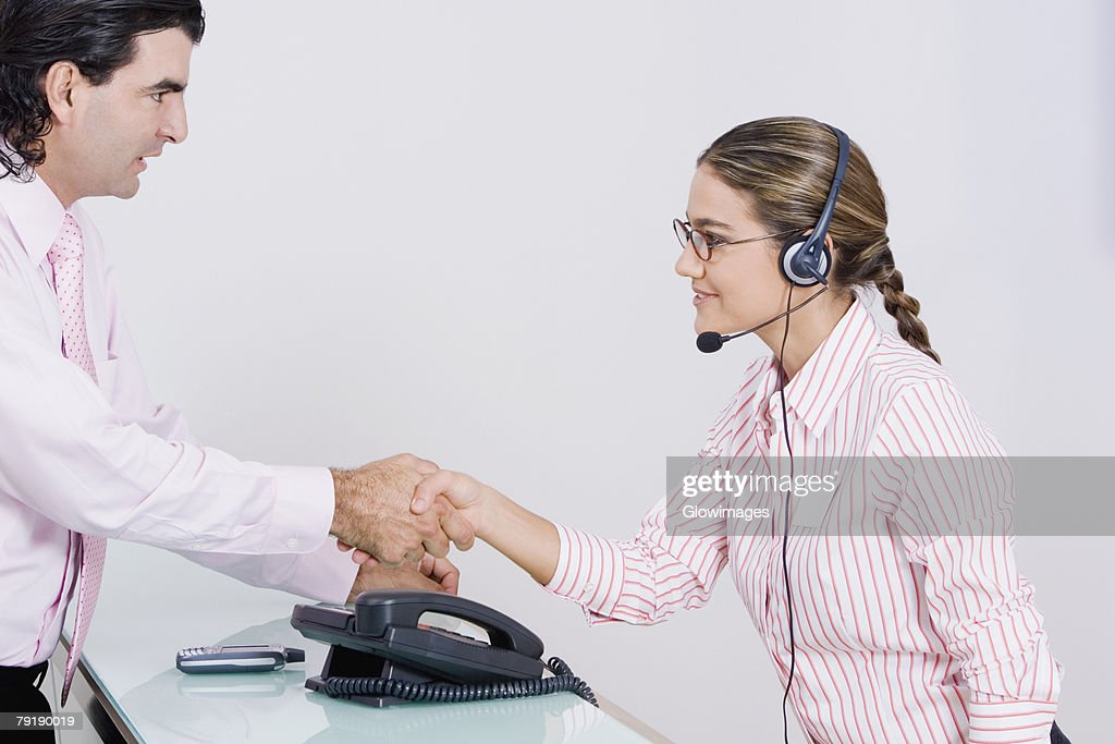 Side profile of a businessman and a businesswoman shaking hands : Foto de stock