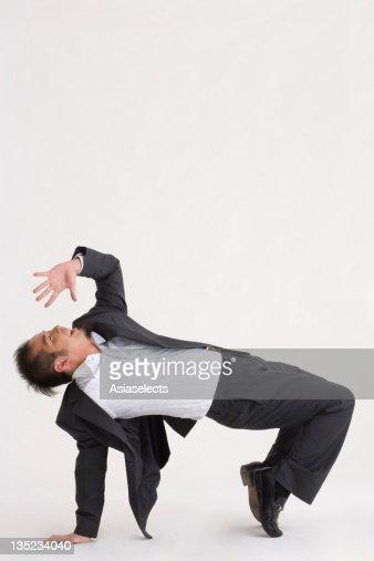 Side profile of a businessman bending over backwards