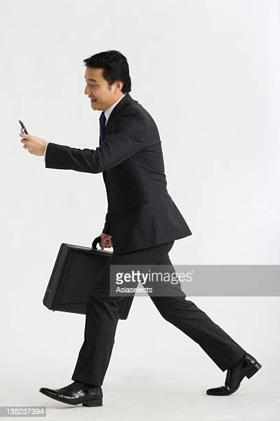 Side profile of a businessman carrying a briefcase
