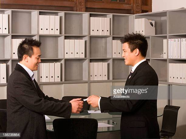 Side profile of a businessman giving a business card to another businessman