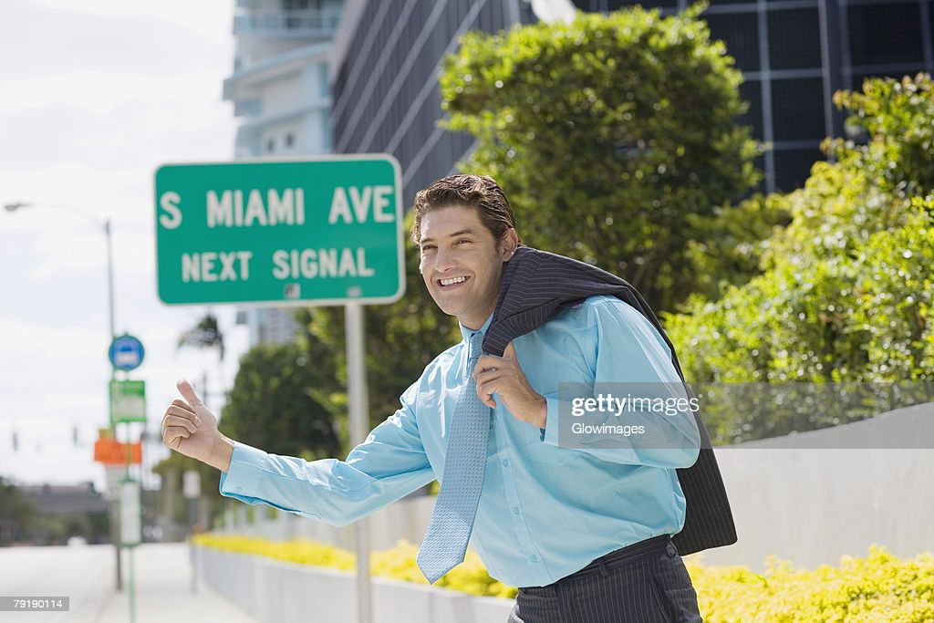 Side profile of a businessman hailing on the road and smiling : Stock Photo
