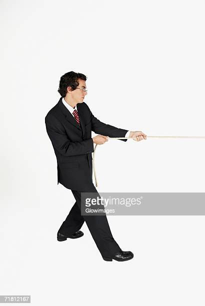 Side profile of a businessman pulling a rope