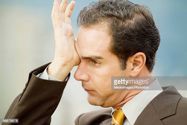 Side profile of a businessman rubbing his eyes