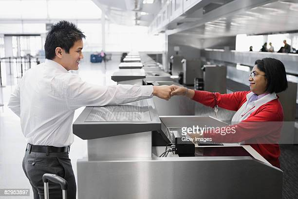 Side profile of a businessman shaking hands with an airline check-in attendant