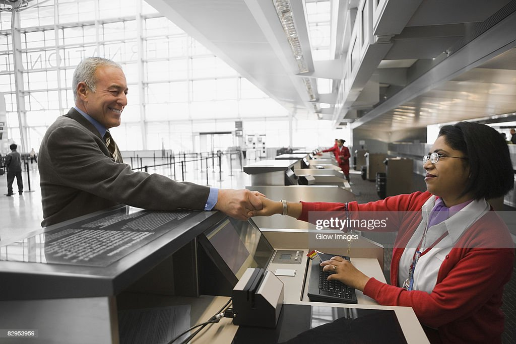 Side profile of a businessman shaking hands with an airline check-in attendant and smiling