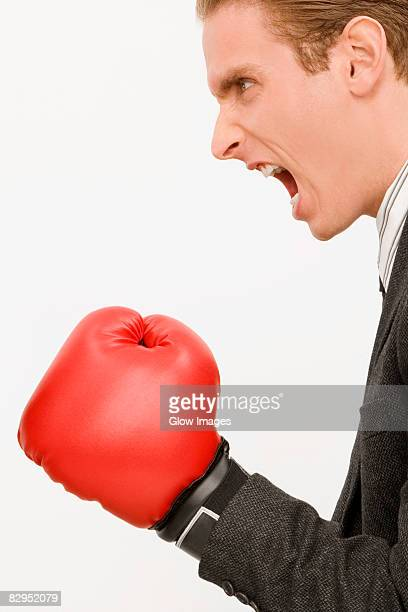 Side profile of a businessman wearing boxing gloves