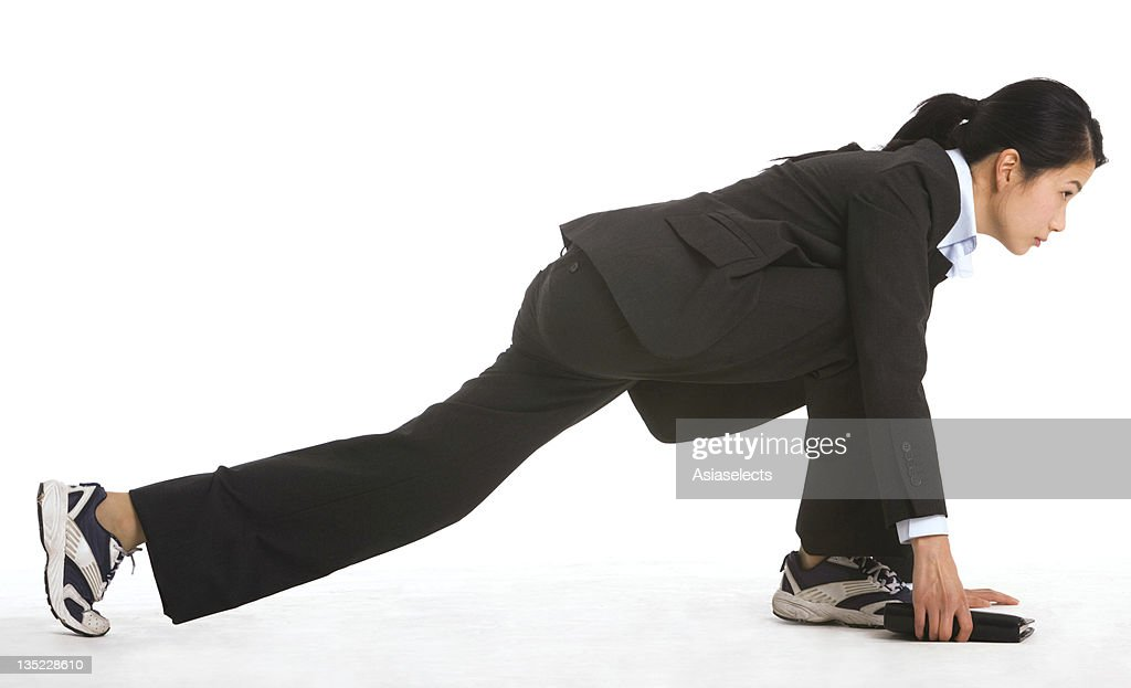 Side profile of a businesswoman exercising : Stock Photo