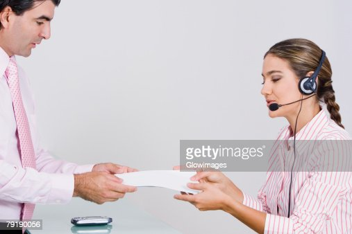 Side profile of a businesswoman giving a document to a businessman : Foto de stock