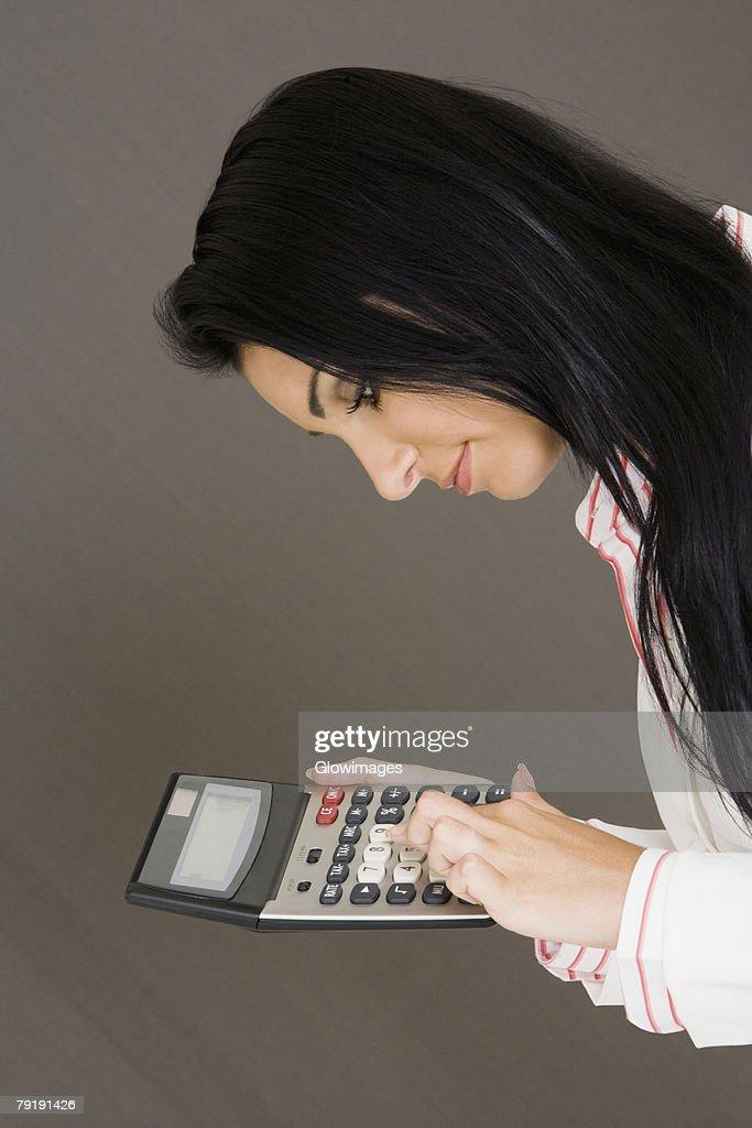 Side profile of a businesswoman holding a calculator : Foto de stock