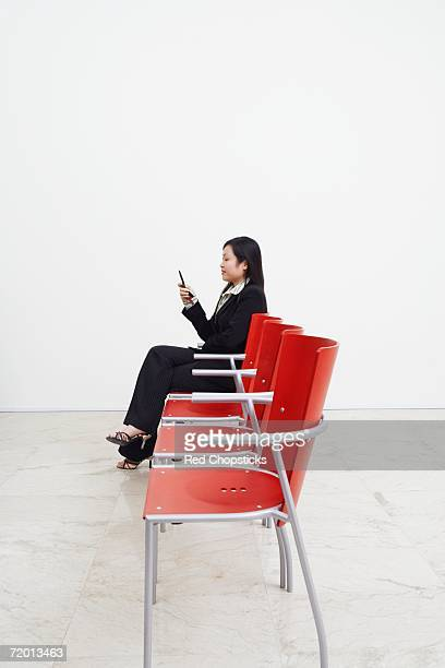 Side profile of a businesswoman looking at a mobile phone