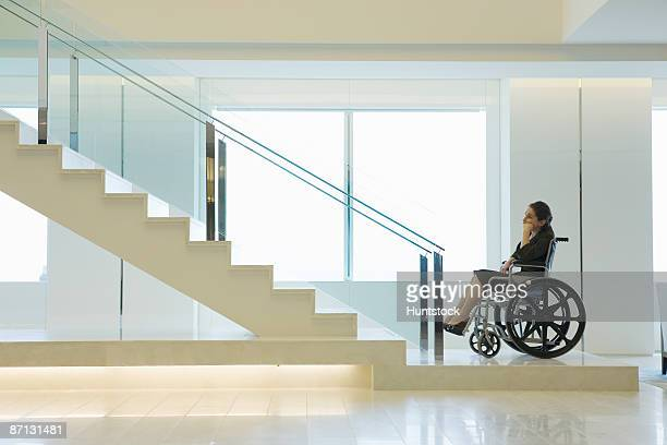 Side profile of a businesswoman on a wheelchair near a staircase