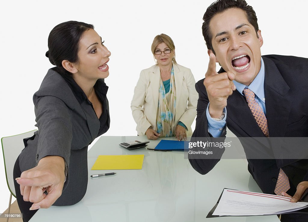 Side profile of a businesswoman pointing at another businessman standing in front of her : Stock Photo