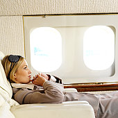 side profile of a businesswoman relaxing in an airplane