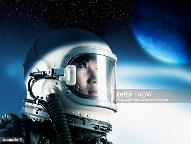 Side profile of a female astronaut wearing a space helmet