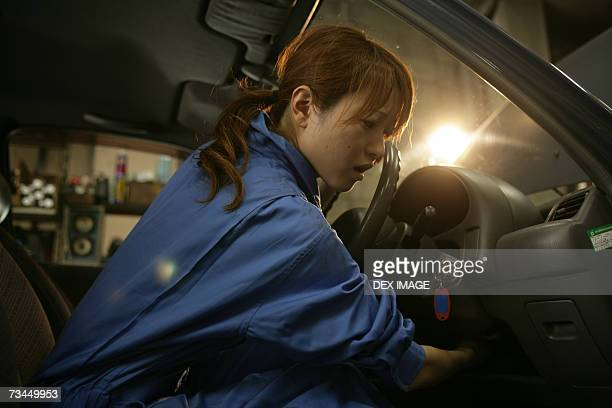Side profile of a female auto mechanic examining a car