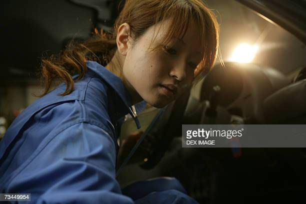 Side profile of a female auto mechanic sitting in a car