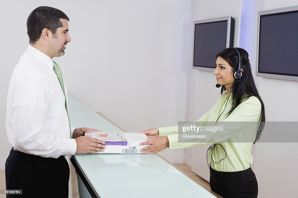 Side profile of a female customer service representative giving books to a businessman : Stock Photo