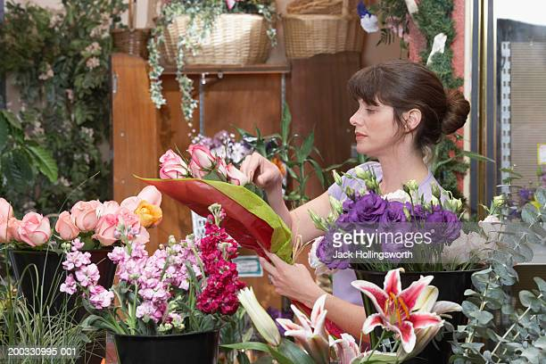 Side profile of a female florist preparing a bouquet in a flower shop