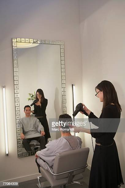 Side profile of a female hairdresser cutting hair of a mid adult man