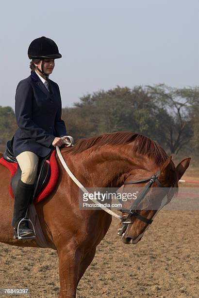 Side profile of a female jockey riding a horse