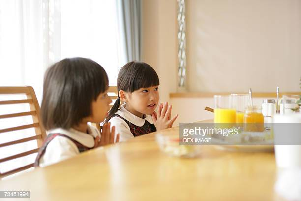 Side profile of a girl and her sister sitting at the dining table and praying