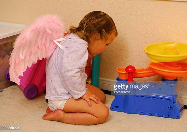 Side profile of a girl kneeling on the floor and looking at a toy
