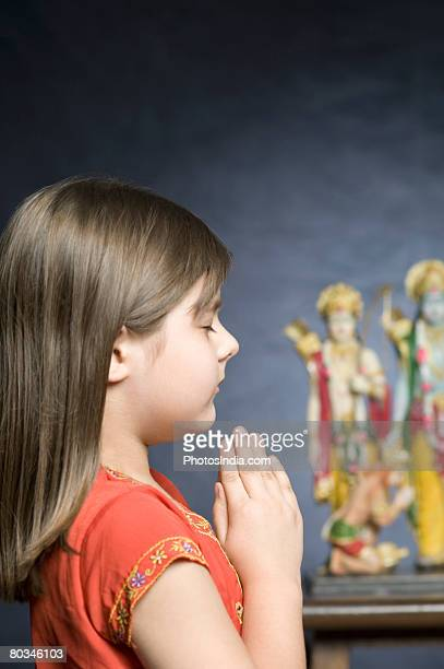 Side profile of a girl praying in front of statues of God