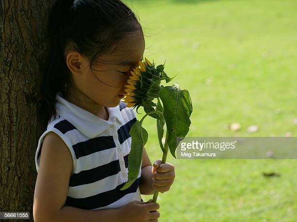 Side profile of a girl smelling a sunflower