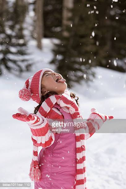 Side profile of a girl sticking out her tongue to catch snowflakes