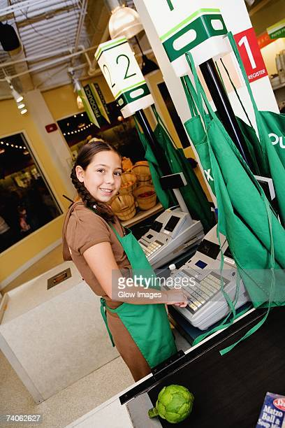 Side profile of a girl using a cash register at the checkout counter