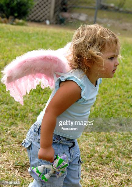 Side profile of a girl wearing fairy wings and holding a toy