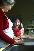 Side profile of a grandmother standing with her granddaughter in the kitchen