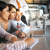 side profile of a group of colleagues viewing a laptop screen