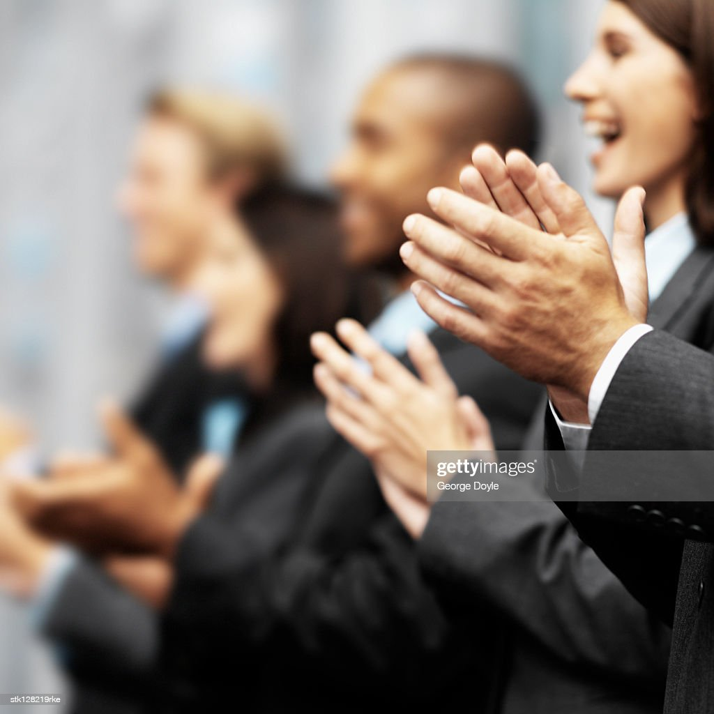 Side profile of a group of young executives clapping (blurred) : Stock Photo