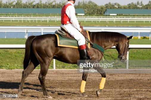 Side profile of a jockey riding a horse on a horseracing track : Foto de stock