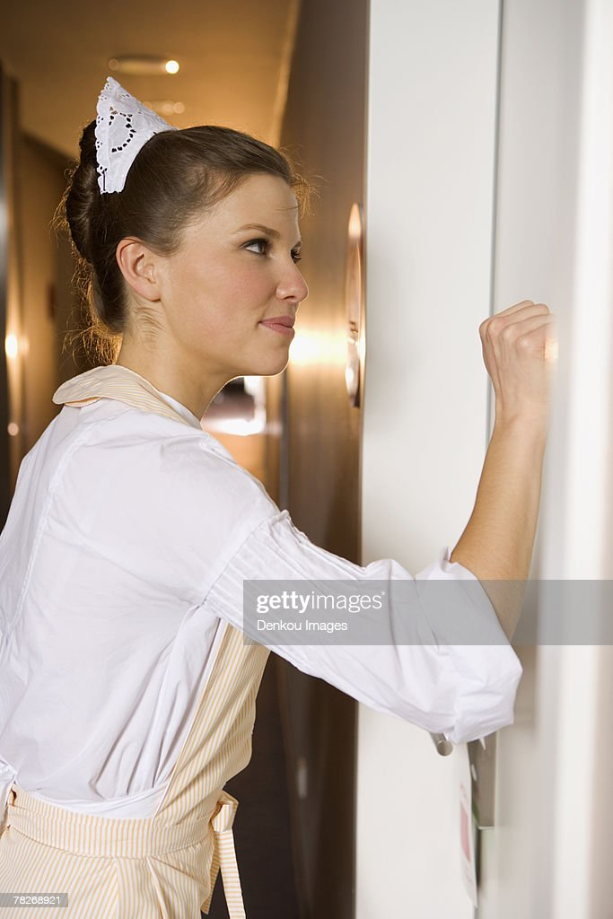 side profile of a maid knocking at a door stock foto getty images. Black Bedroom Furniture Sets. Home Design Ideas