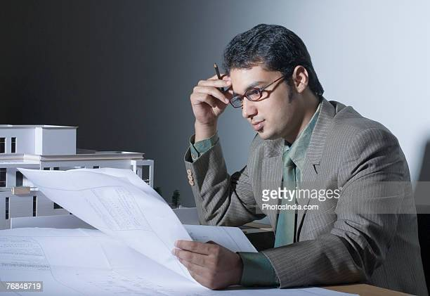 Side profile of a male architect looking at a blueprint and thinking