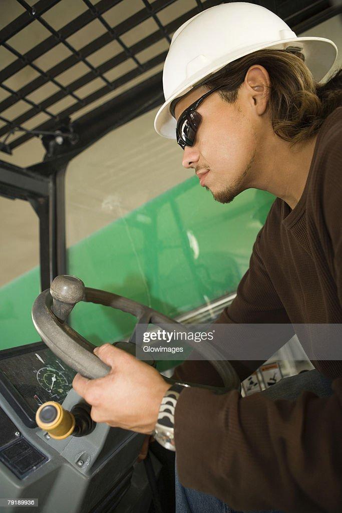 Side profile of a male construction worker operating a crane : Foto de stock