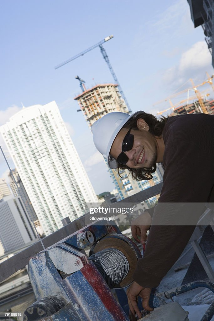 Side profile of a male construction worker working at a construction site : Foto de stock