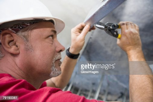 Side profile of a male construction worker working with a wrench : Stock Photo