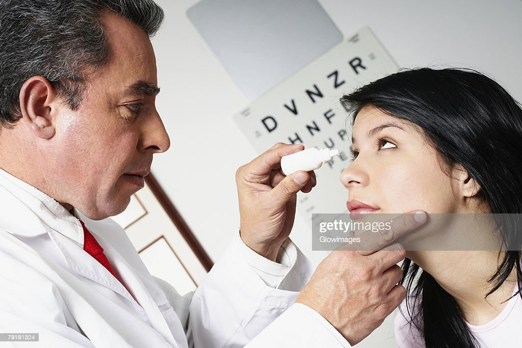 Side profile of a male doctor putting eye drops in a young woman's eye