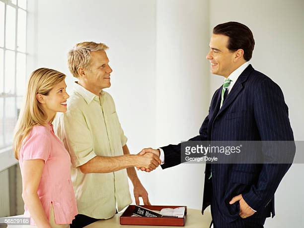 side profile of a male real estate agent shaking hands with a mid adult man