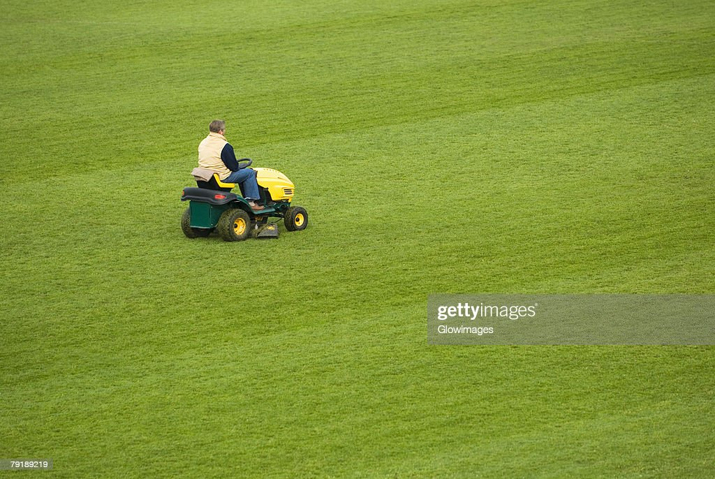 Side profile of a man mowing grass with a lawn mower in a field : Stock Photo