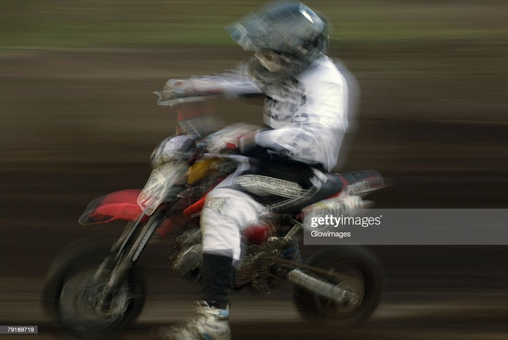 Side profile of a man riding a motorcycle in a sports race : Stock Photo