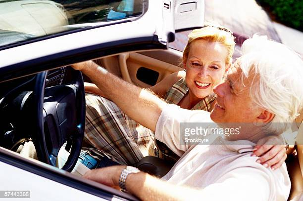 side profile of a mature couple sitting in a convertible car