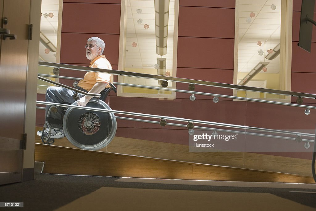 Side Profile Of A Mature Man Sitting In A Wheelchair On A Wheelchair Ramp :  Stock