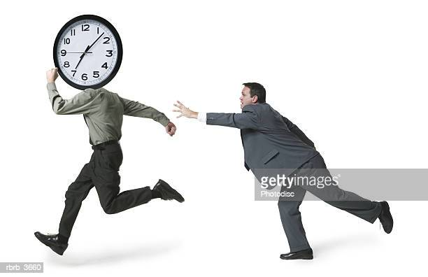 Side profile of a mature men running holding a clock