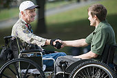Two disabled men shaking hands and smiling